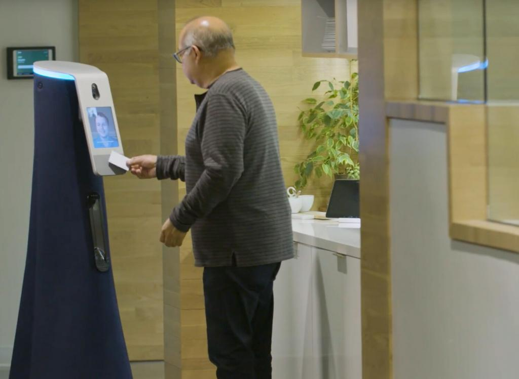An employee badges in on the Cobalt security robot